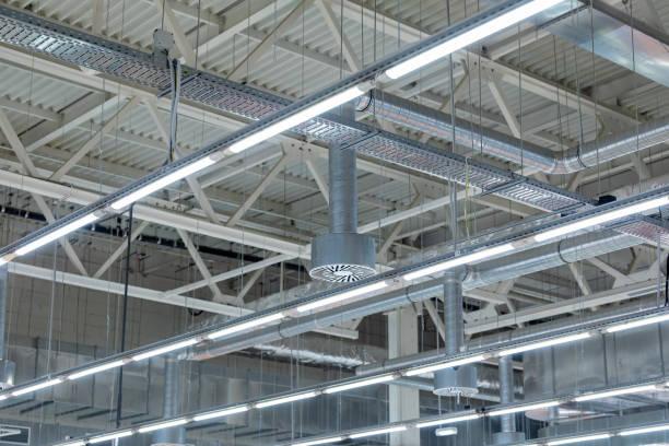 luminaires et chemins de câbles à l'intérieur d'une usine